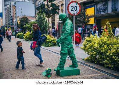 COLOMBIA - APRIL 26: Cute small kid plays and smiles with a toy soldier human statue, April 26, 2018 in Bogota, Colombia
