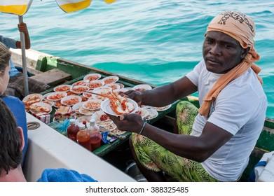 COLOMBIA, CIRCA JAN 2010: Unidentified fisherman sell fresh lobster to tourist in rosario island archipelago near Cartagena.