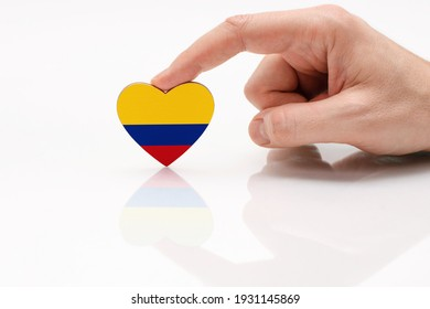 Colombia flag. Love and respect Colombia. A man's hand holds a heart in the shape of the Colombia flag on a white glass surface. The concept of patriotism and pride