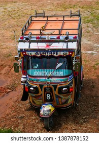 """GUATAPÉ, COLOMBIA - MARCH 28, 2019: Colorful Tuc Tuc transport painted by unknown artist, (The sign, in spanish language, says """"How to play -or touch- Guatapé"""")."""