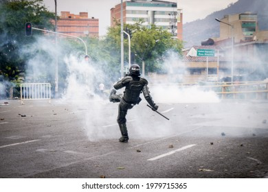 MEDELLÍN, COLOMBIA - MAY 01, 2021: Member of the army kicking a tear gas bomb in demonstrations in the streets of Medellin.