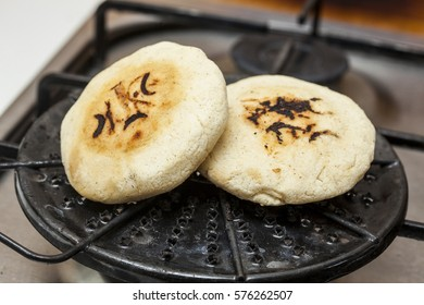 Colombian arepas being roasted on a round grill