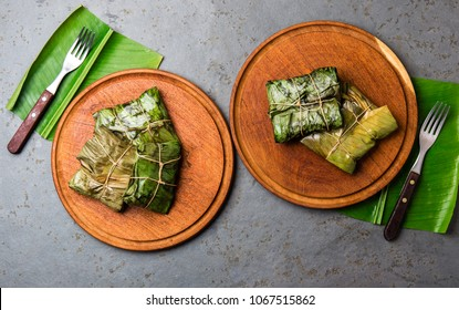 COLOMBIAN, CENTRAL AMERICAN FOOD. Tamales wrapped in banana palm tree leaves on wooden plates, gray stone background.