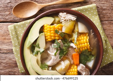 Colombian cuisine: ajiaco soup with chicken and vegetables close up in a bowl on the table. horizontal view from above