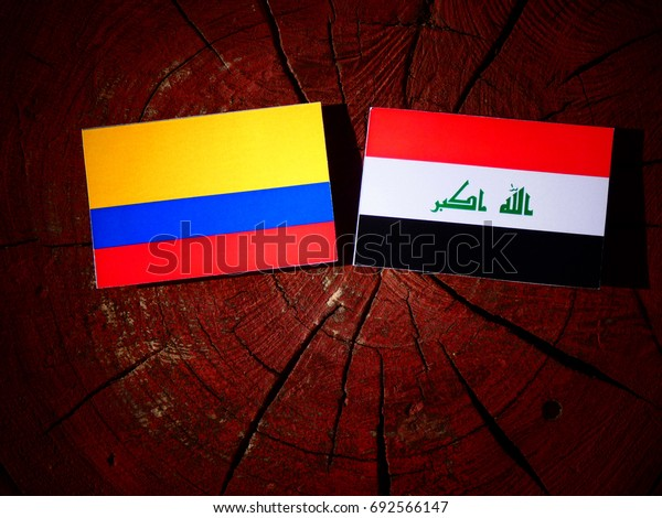 Colombian flag with Iraqi flag on a tree stump isolated
