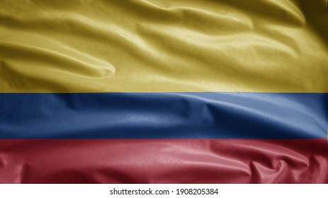 Colombian flag waving in the wind. Close up of Colombia banner blowing, soft and smooth silk. Cloth fabric texture ensign background. Use it for national day and country occasions concept.