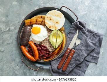 La comida colombiana. Bandeja paisa, plato típico en la región de Antioquia de Colombia - chicharrón (vientre de cerdo frito), morcilla, salchicha, arepa, frijoles, plátano frito, huevo aguacate y arroz.
