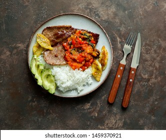colombian food. El Bistec a la Criolla  -  traditional beef steak with tomatoes sauce, rice, avocado, bananas fries
