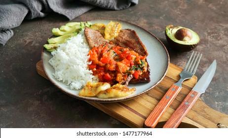 comida colombiana. flanksteak o Sobrebarriga en salsa criolla - plato colombiano tradicional - carne de buey con salsa de tomates, arroz, aguacate, papas fritas bananas