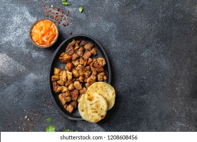 COLOMBIAN FOOD. Fried pork CHICHARRON, AREPAS and colombian tomato sauce. Top view. Black background.