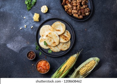 COLOMBIAN FOOD. Maize AREPAS and fried pork chicharron ans colombian tomato sauce. Top view. Black background.