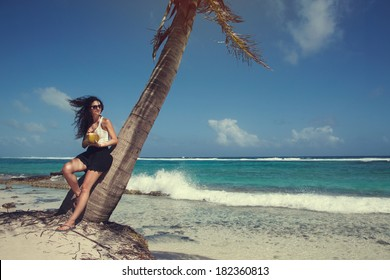Colombian Girl in Vacation Drinking a Coconut Drink Under a Palm Tree