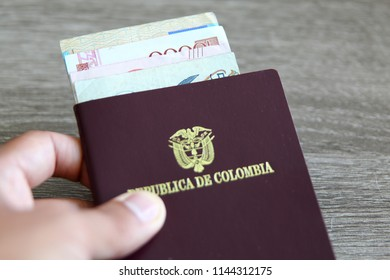 Colombian passport with bank notes over a light grey wooden background