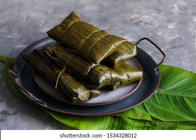 Colombian Tamales wrapped in banana palm tree leaves,  Venezuelan christmas food - hallaca - corn dough stuffed with a stew of pork and chicken