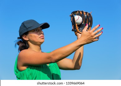 Colombian woman with glove and cap catching baseball outdoors with blue sky