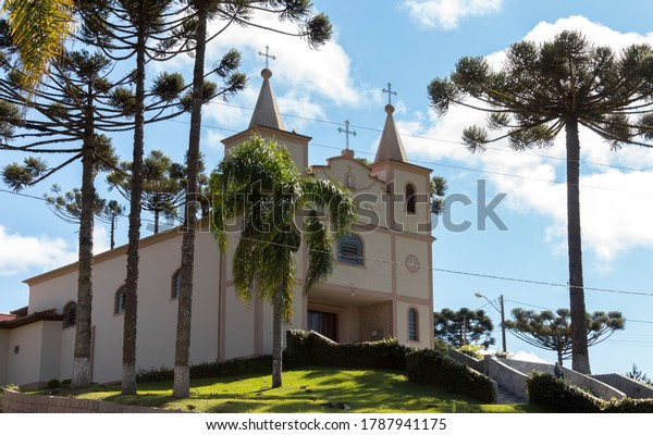 "Colombo, Paraná, Brazil - August 01, 2020. Chapel ""Santa Gemma Galgani"". A small church in Colombo's rural area. Side view. Araucaria (trees) surround the church, two towers and three crosses."