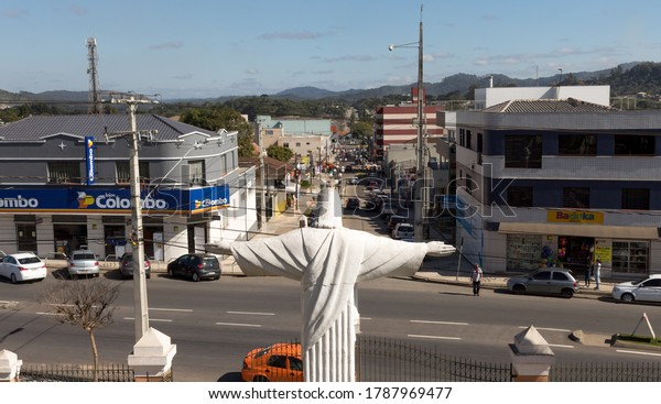 Colombo, Paraná, Brazil - August 01, 2020. Jesus Christ statue with open arms blessing the city downtown. The statue it's completely white and resemble the famous Christ the Redeemer. Back view.
