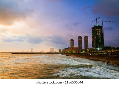 Colombo, Sri Lanka. Cityscape of Colombo, Sri Lanka with modern buildings at sunset. Ocean waves at night and cloudy sky. People at promenade area