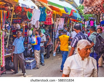 COLOMBO, SRI LANKA - DECEMBER 6, 2016: Narrow rows of clothes department of Pettah market are crowded and noisy, the sellers advertise their goods, yelling the cheap prices , on December 6 in Colombo.