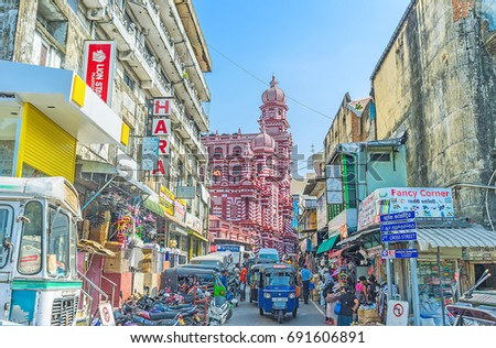 COLOMBO, SRI LANKA - DECEMBER 7, 2016: Towers and domes of Jami-Ul-Alfar Mosque - Red Masjid, located behind numerous tuk tuks and stalls in narrow street of Pettah market, on December 7 in Colombo.