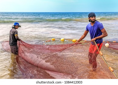 Colombo, Sri Lanka - January 14, 2018. Two fishermen get from the sea to the shore a trawl with fish on a sunny day