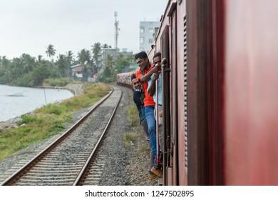Colombo, Sri Lanka - July 26, 2018: Many people clinging to driving train