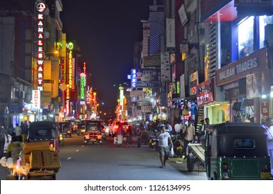 Colombo, Sri Lanka, March 29, 2018 - View of the bustling and noisy Main Street in Pettah Market district at night with some mutlicolored neon lights commercial signs.