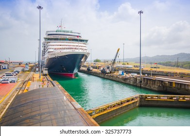 "COLON, PANAMA - APRIL 15, 2015: The Queen Victoria navigating the Panama Canal, is classified as a ""Panamax"" vessel, the largest the canal can accommodate. Gatun Locks."