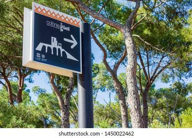 COLONIA GUELL-SANTA COLOMA DE CERVELLO, SPAIN- JUNE 18,2019: Colonia Guell display logo sign, company town. Sign information to Church, Cripta designed by Antoni Gaudi.