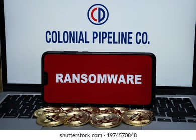 Colonial Pipeline Co logo on the blurred background and word RANSOMWARE on the smartphone in front. Stafford, United Kingdom, May 16, 2021.