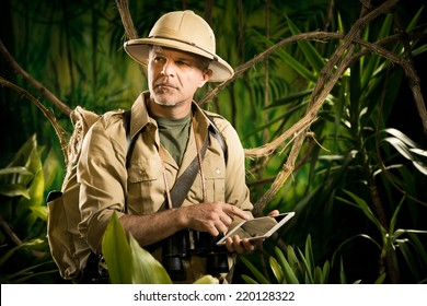 Colonial style adventurer with digital tablet exploring jungle wilderness.