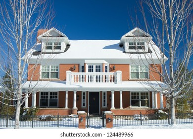 Colonial Style luxury home after a snowstorm.