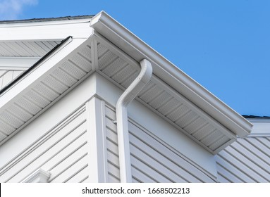 Colonial white fiber cement horizontal vinyl lap siding, soffit with ventilation,  gutter and guard, eaves with elbow, drip, on a new construction American single family home