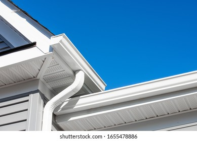 Colonial white gutter guard system,  soffit providing ventilation to the attic, with gray vinyl horizontal siding at a luxury American single family home neighborhood USA