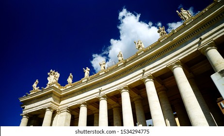 Colonnade of the Basilica of Saint Peter seen in perspective from below. Created by Gian Lorenzo Bernini, it has 140 statues on the top