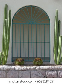 Colonnade in a building facade, protected by a grating and flanked by cacti