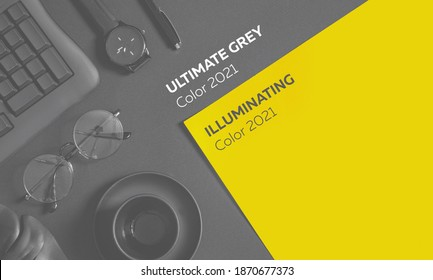 Color 2021 illuminating and Ultimate Gray. Desk with laptop, eye glasses, pen and a cup of coffee. Top view with copy space. totally black