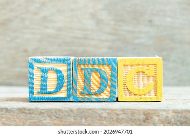 Color alphabet letter block in word DDC (Abbreviation of Division of disease control,  Direct digital control, Display Data Channel or Dewey Decimal Classification) on wood background