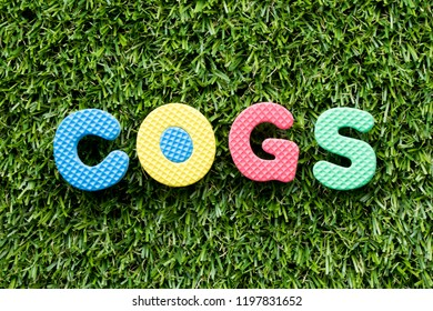 Color alphabet letter in word COGS (Abbreviation of Cost of goods sold) on artificial green grass background