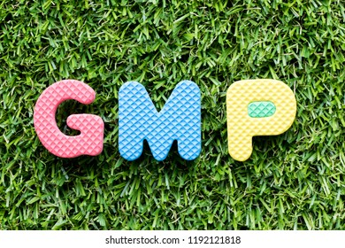Color alphabet letter in word GMP (Abbreviation of good manufacturing practice) on artificial green grass background