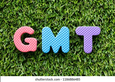 Color alphabet letter in word GMT (abbreviation of Greenwich Mean Time) on artificial green grass background
