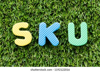Color alphabet letter in word SKU (abbreviation of stock keeping unit) on artificial green grass background