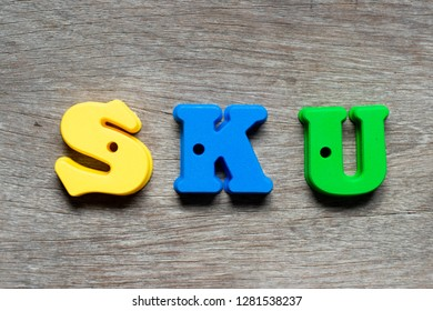 Color alphabet letter in word SKU (abbreviation of stock keeping unit) on wood background
