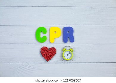 Color alphabet in word CPR abbreviation of Cardiopulmonary resuscitation heart and clock on white wood background. Medical concept.