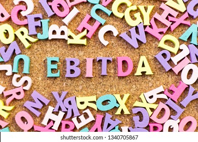Color alphabet in word EBITDA (abbreviation of earnings before interest, taxes, depreciation and amortization) with another letter as frame on cork board background