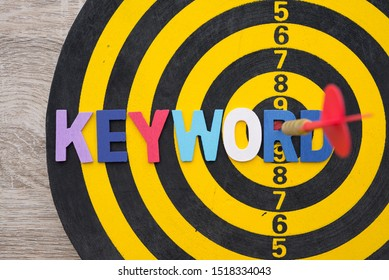 Color alphabets KEYWORD on dartsboard background with red arrow hit center of target. Advertising business and marketing concept. Keyword research is important SEO activity if would like page to rank.