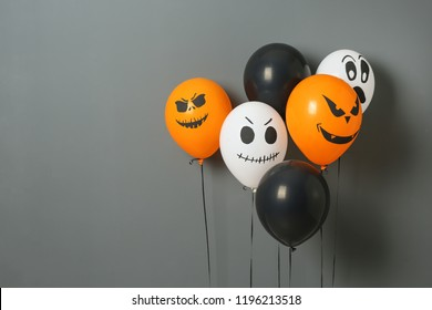 Color balloons for Halloween party on gray background. Space for text