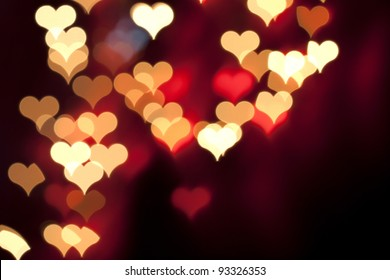 Color Bokeh on a dark background with hearts for use in graphic design