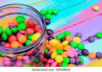 color candy on color wooden table