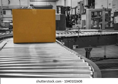 Color cardboard box moves on black and white conveyor belt rolls in shipping dock